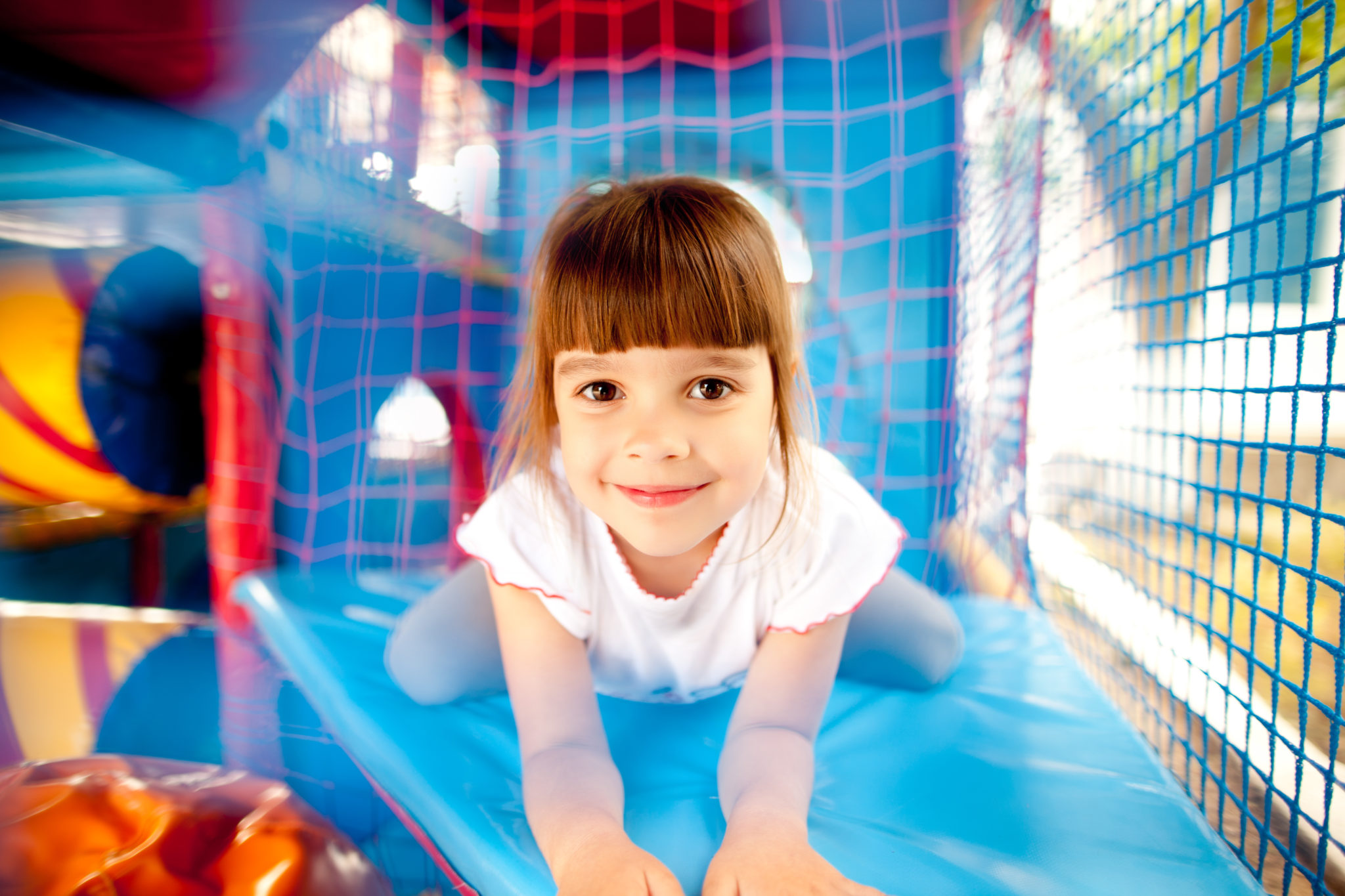 Colorful inflatables playground where girl with brown hair is smiling and laying on blue surface